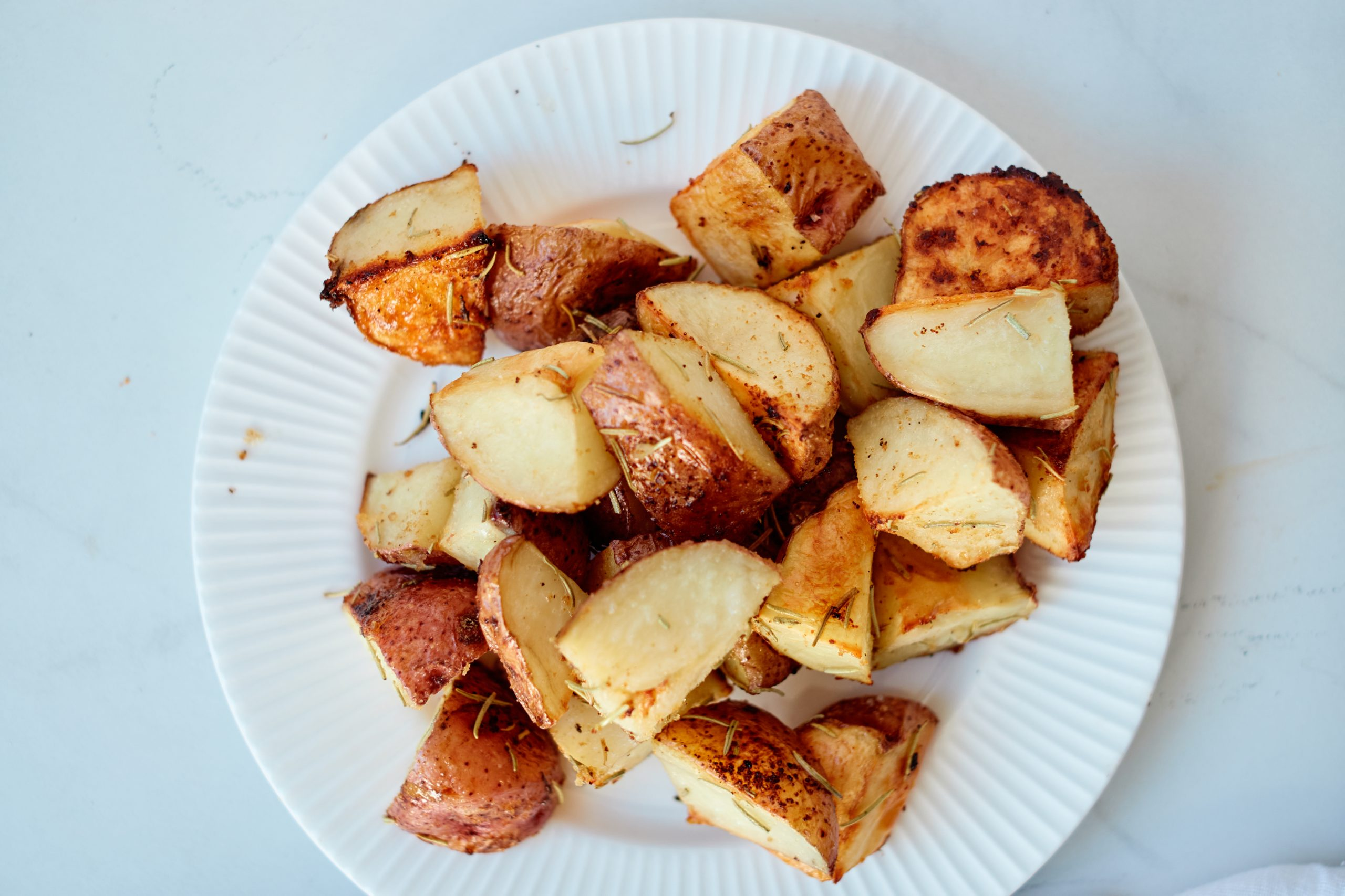 roasted potatoes with rosemary and garlic on a white plate