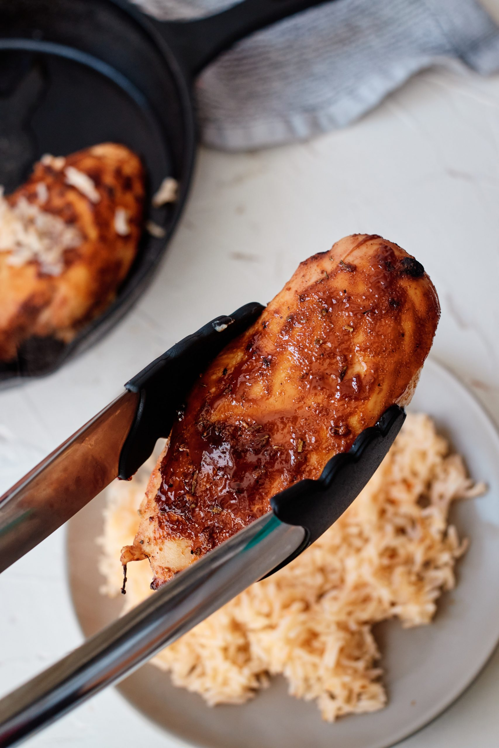Cuban-Style Sautéed Chicken held by tongs being set down on a plate on top of rice