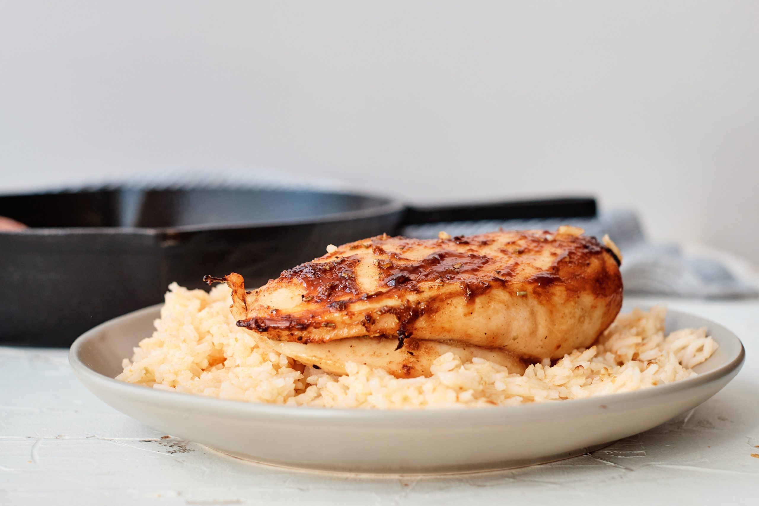 Cuban-Style Chicken on a bed of rice on a plate with a cast iron skillet in the background