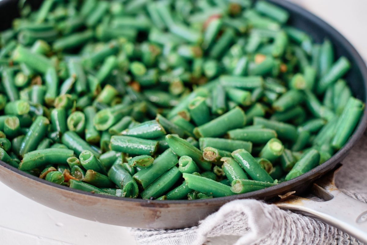 saute pan filled with green beans stir-fried in a sesame soy glaze