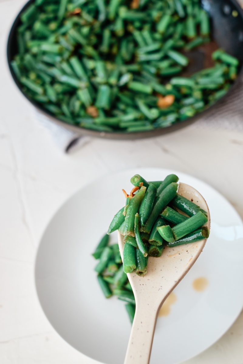 A wooden spoon holding a serving of green beans up close, over a white plate. Sauté pan of green beans in the background