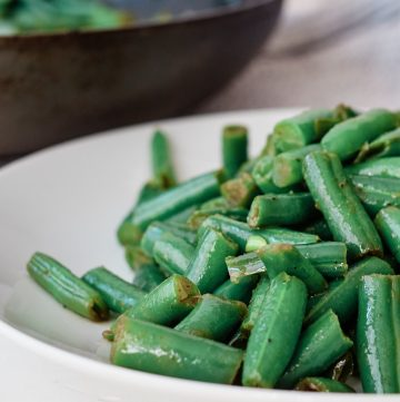 White plate filled with stir-fry green beans with a sauce pan in the background