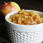 A white bowl filled with diced apples coated in a cinnamon brown sugar mixture. A red apple is in the background