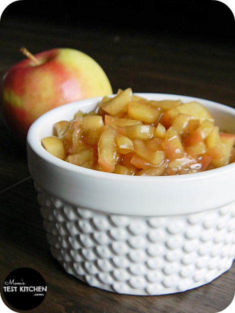 A white bowl filled with apple pie dip. A red apple is in the background