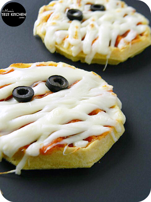 Two waffles topped with pizza sauce, mozzarella cheese and black olives to make a Mummy Waffle Pizza face