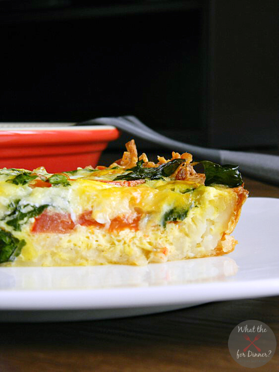 An unclose photo of a slice of Caprese Florentine Quiche sitting on top of a white plate with a red pie plate and spatula in the background