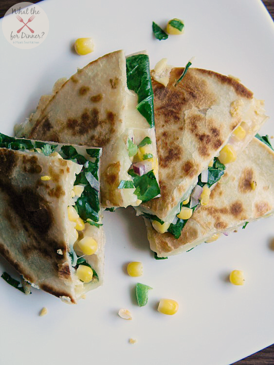 Veggie Quesadillas filled with spinach and corn salsa cut into triangles and stacked on a white plate