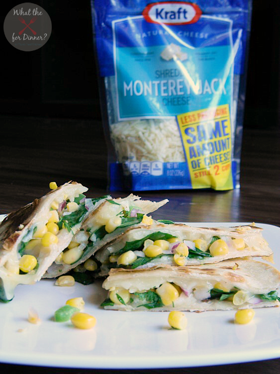 Veggie Quesadillas filled with spinach and corn salsa cut into triangles and stacked on a white plate with a bag of Kraft Monterrey Jack Cheese in the background