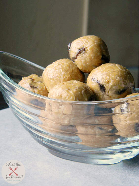 A clear bowl filled with oatmeal raisin cookie energy balls sitting on a table