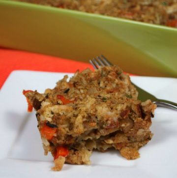 A portion of Stuffing Casserole on a white plate with a green baking dish in the background filled with the casserole
