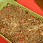 A green baking dish filled with Stuffing Casserole sitting on a red place setting