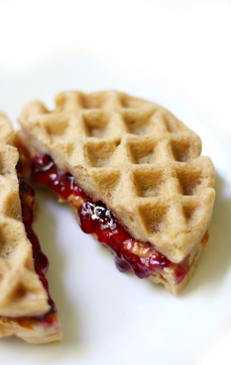Peanut Butter and Jelly Waffle Sandwich cut in half on a white plate