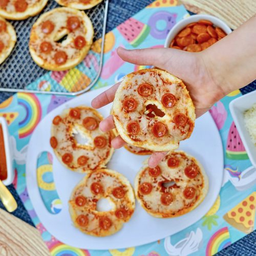 A childs hand holding an pepperoni bagel bite in the foreground. 3 Bagel bites on a white plate in the background, with tomato sauce in a bowl with a spoon. Mozzarella cheese in a bowl. An Air fryer rack with three more bagel bites sitting next to the plate.
