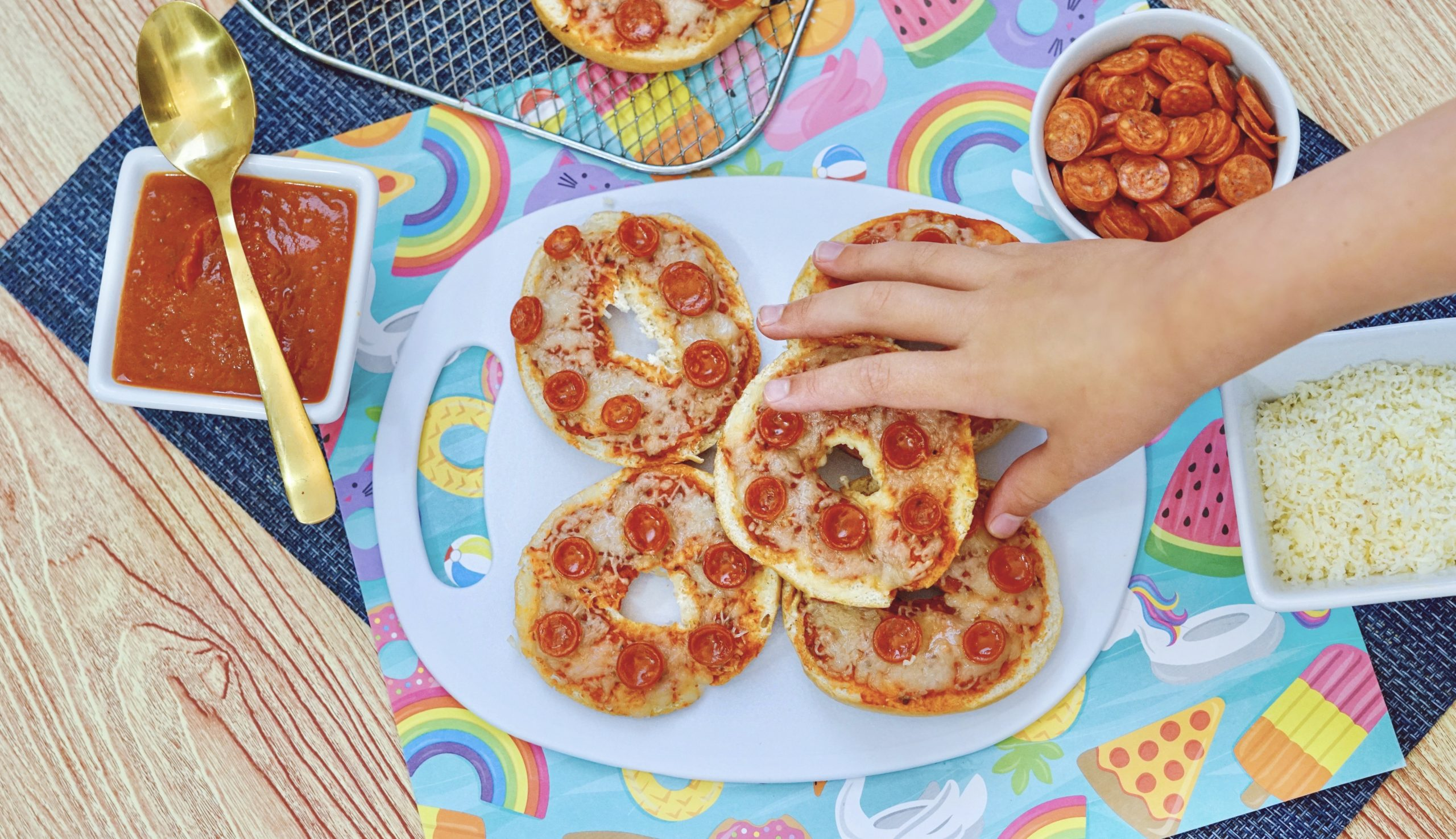 A childs hand grabbing a pepperoni bagel bite in the foreground. 3 Bagel bites on a white plate in the background, with tomato sauce in a bowl with a spoon. Mozzarella cheese in a bowl. An Air fryer rack with three more bagel bites sitting next to the plate.
