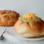 A bread bowl sitting on a white plate, filled with soup and topped with cheddar cheese. A silver dinner spoon is next to the plate. Another loaf of bread for a bread bowl is sitting in the background