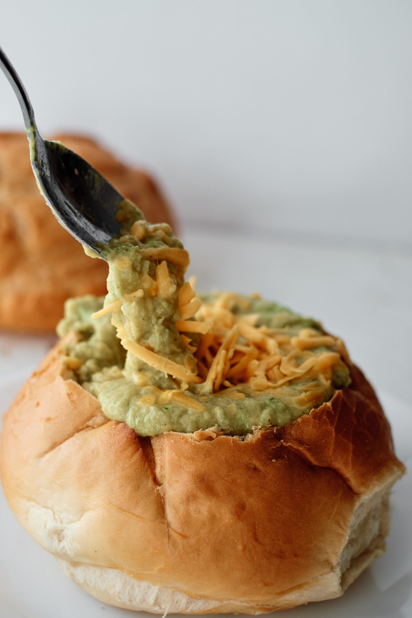 A bread bowl filled with soup, topped with shredded cheddar cheese, with a silver spoon picking up a scoop