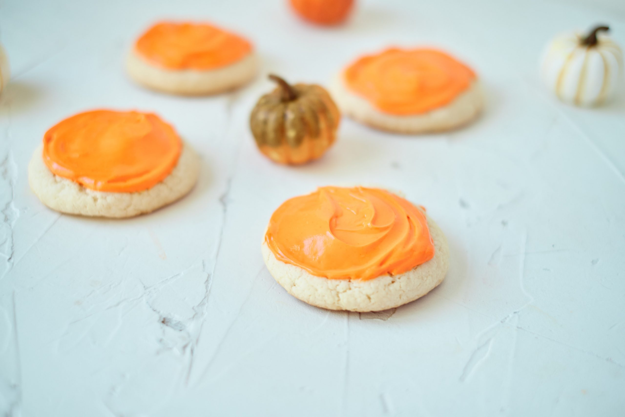 Four Vanilla Pumpkin Cookies on a white table with small pumpkins in the background