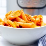 a white bowl filled with baby carrots sitting in front of an instant pot