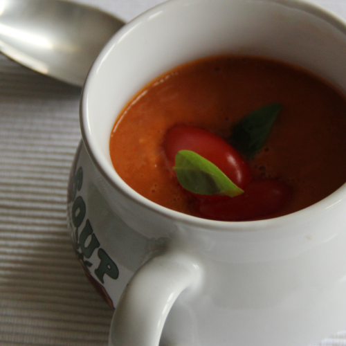 a white soup mug filled with tomato soup with a silver spoon
