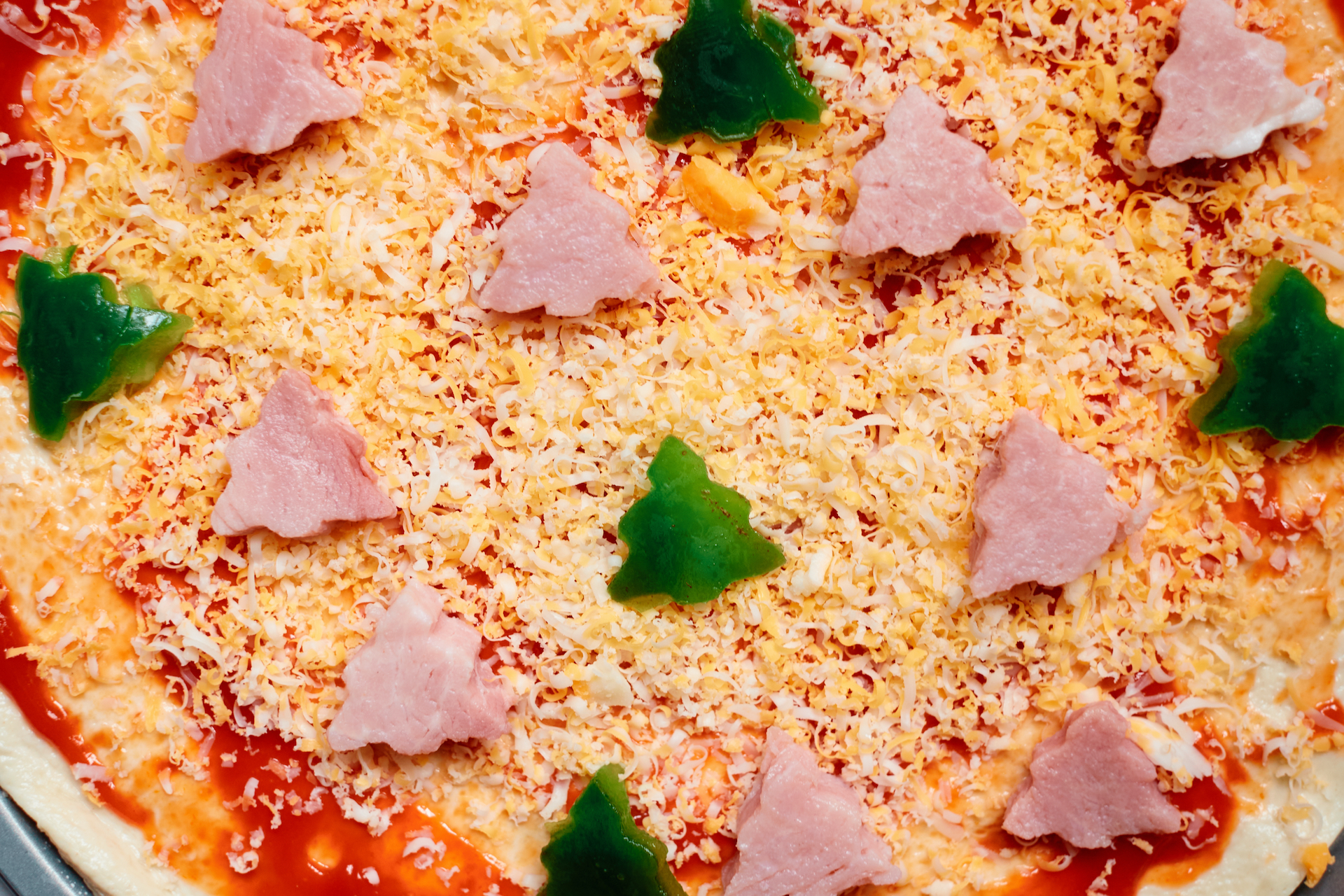 Christmas tree shaped ham and green pepper slices topped on a pizza ready to be baked