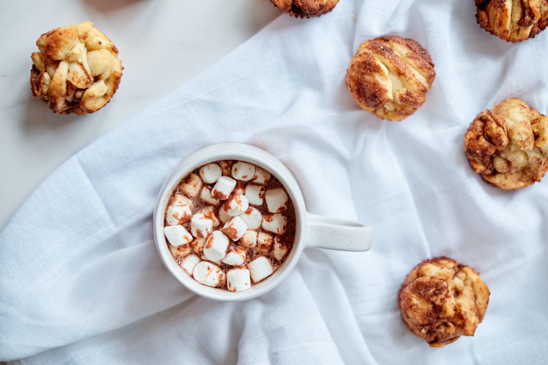 a cup of hot chocolate with marshmallows sitting on a white cloth surrounded by muffins