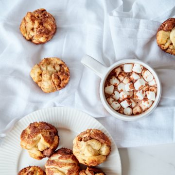 Monkey Bread Muffins sitting on a white towel next to a mug full of hot chocolate