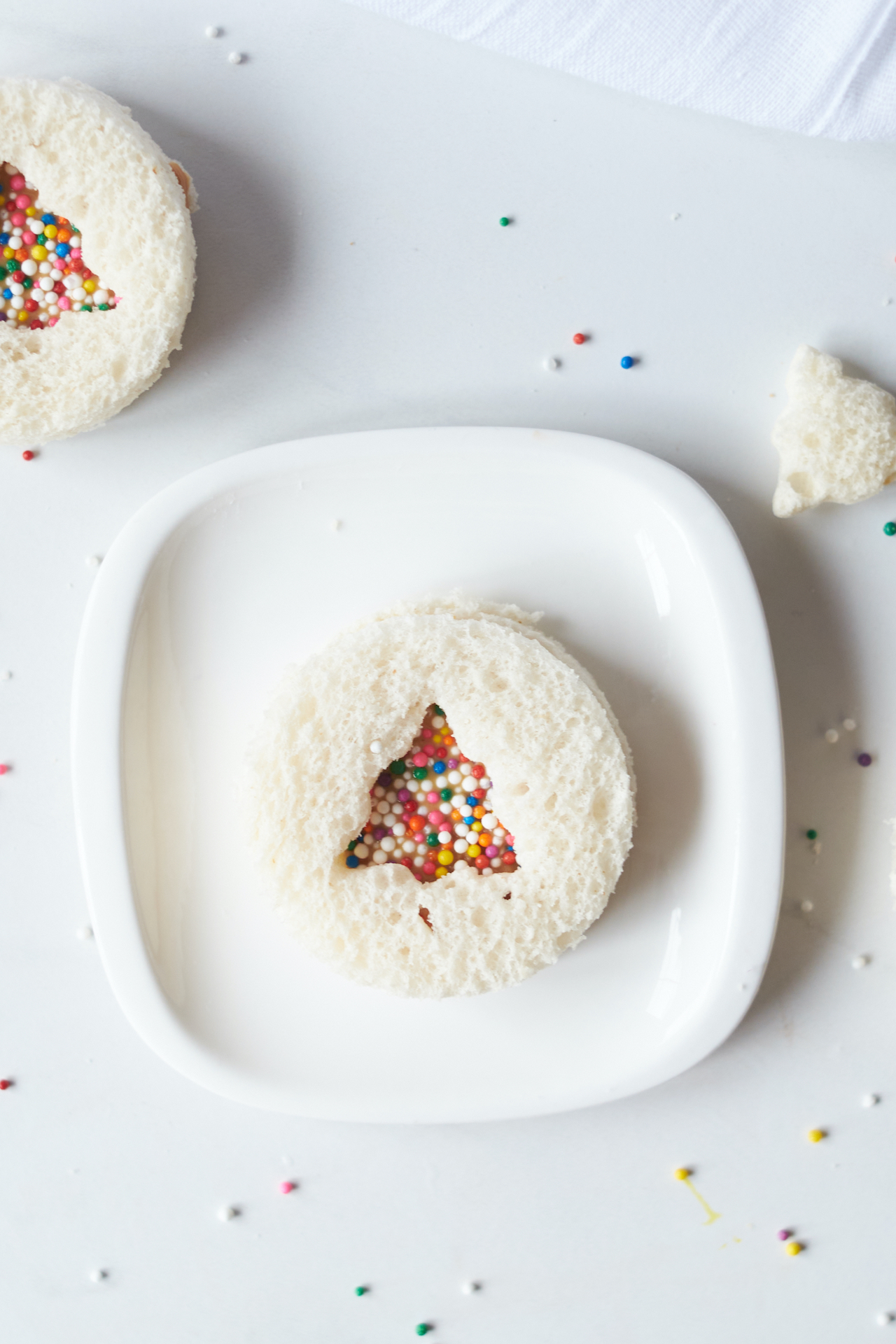a homemade Uncrustables sitting on a white plate with color sprinkles surrounding the plate