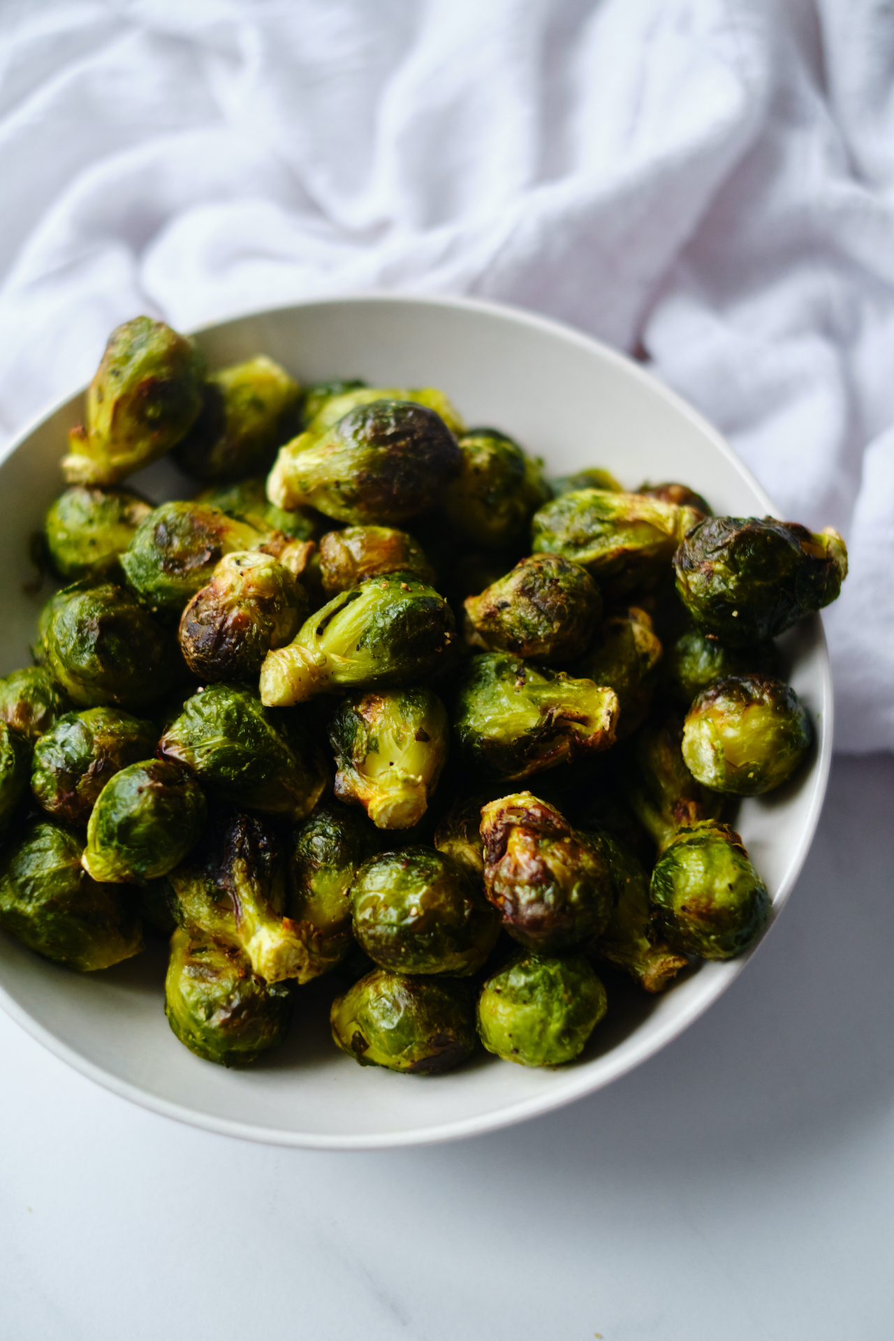 a white bowl filled with air fryer Brussels sprouts sitting next to a white kitchen towel