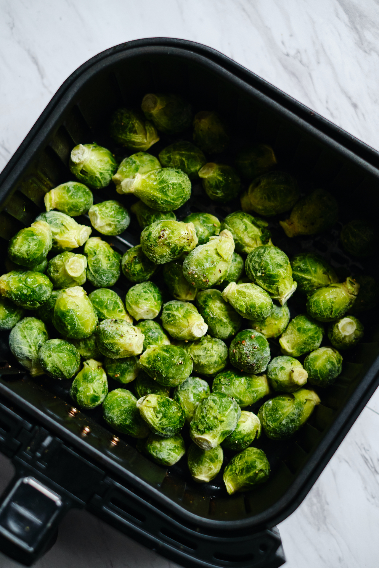sprouts in the basket of an air fryer prior to cooking
