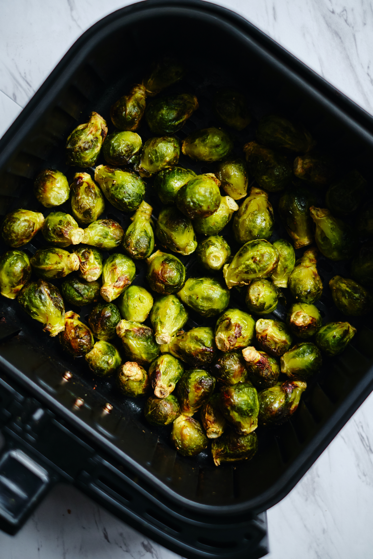 brussels in the basket of an air fryer after being cooked
