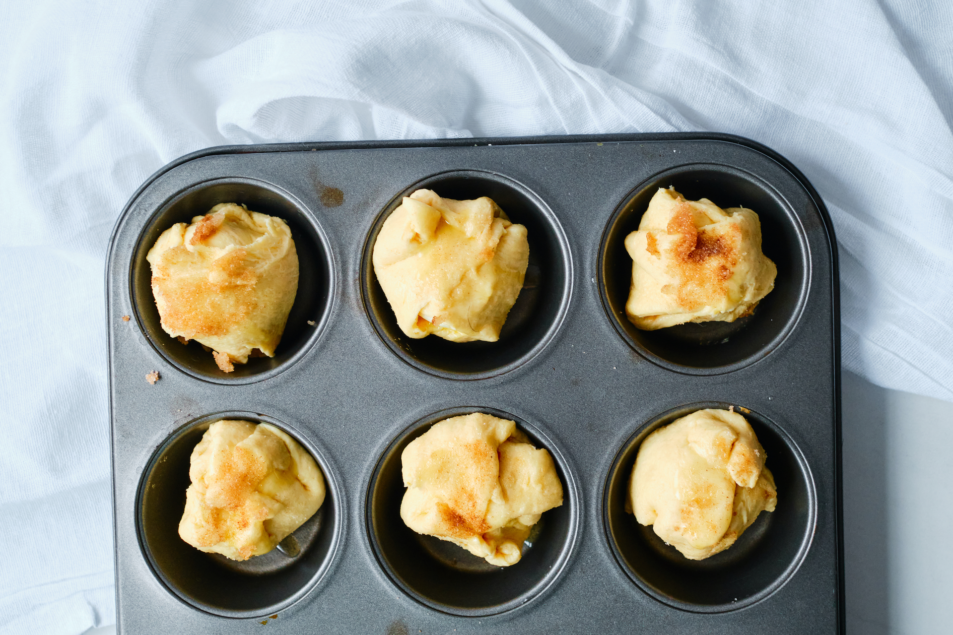 uncooked rolls sitting in a muffin tin