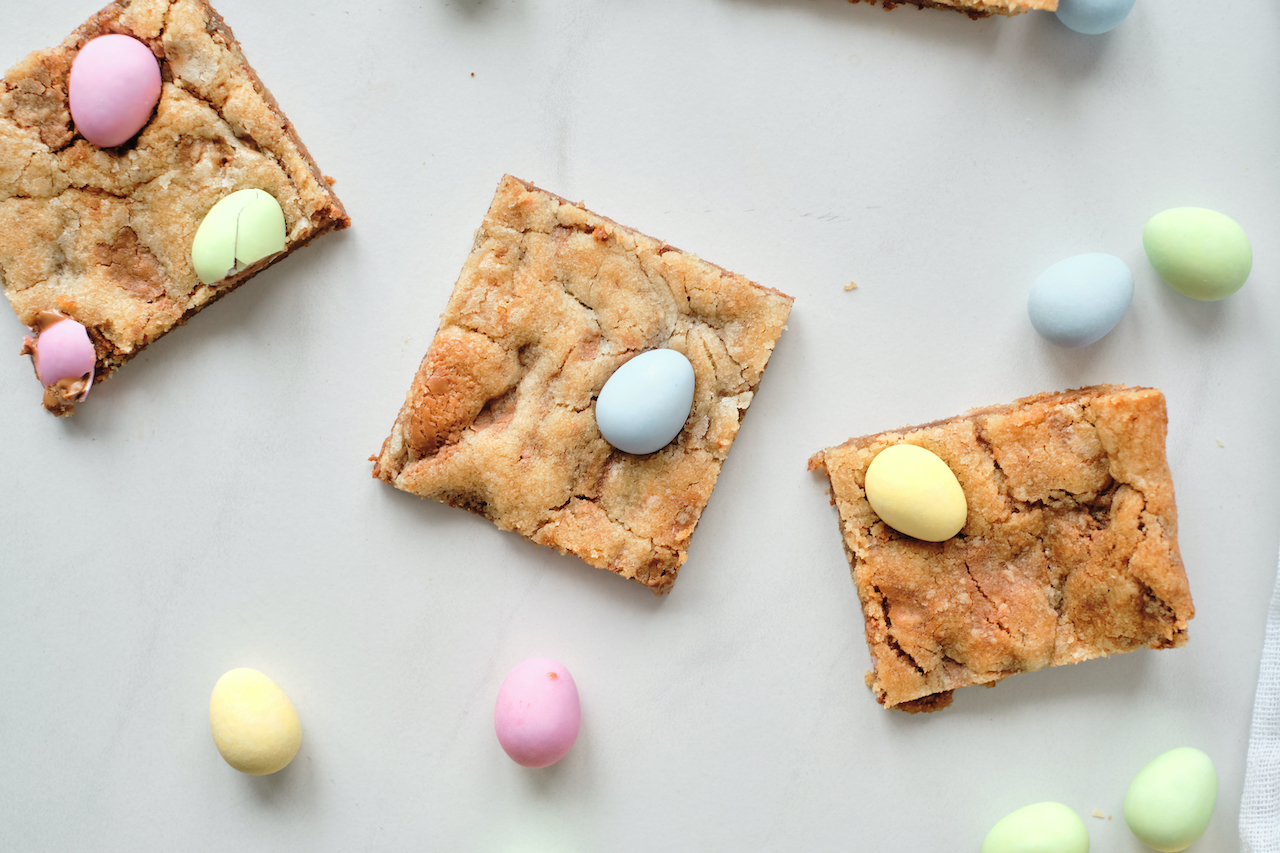 three cookie bars on a white background with extra mini eggs around them