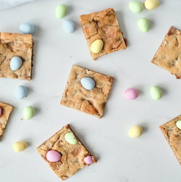 seven mini egg cookie bars sitting on a white background surrounded by mini egg candies