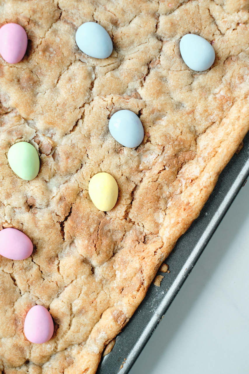 full baking sheet with uncut cookies topped with Easter egg candy