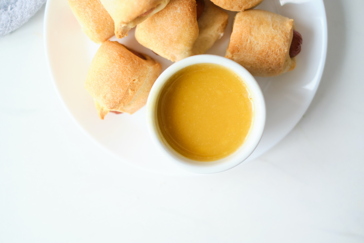 a white bowl of homemade honey mustard sitting on a white plate with pigs in a blanket